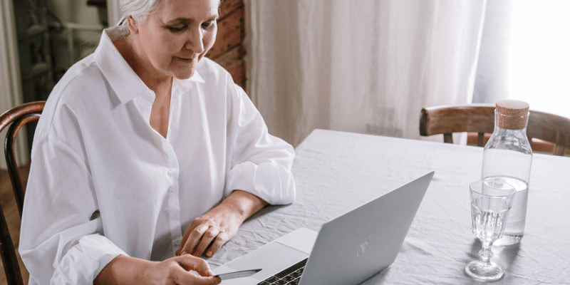 elderly woman on laptop in assessment conversation with clinician